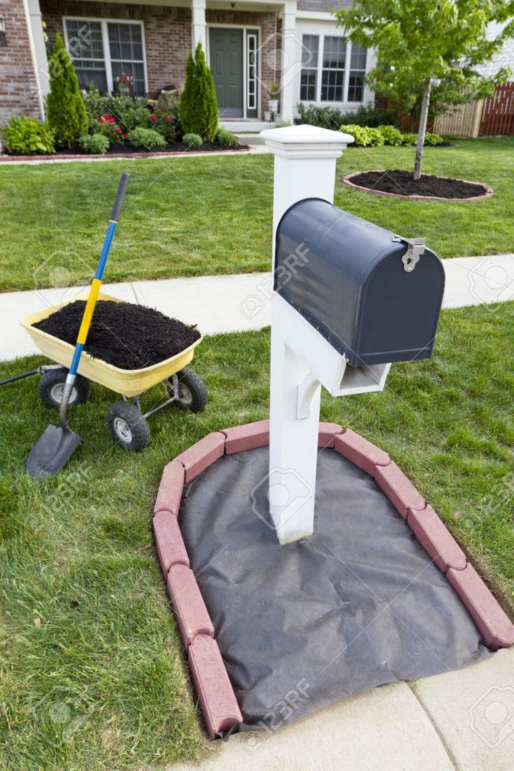 Laying Mulch Around The Mailbox And Placing Edger Bricks. Stock ...