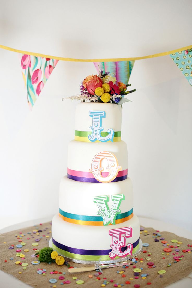 A traditional 4 tier wedding cake decorated with different coloured bright ribbons & and LOVE letters for each tier, standing on a table of scattered buttons - Dasha Caffrey - A colourful village hall wedding in Kent with lots of DIY and a tea length wedding gown. Photography by Dasha Caffrey.