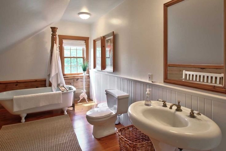 Huge bathroom with pedestal sink and clawfoot tub.