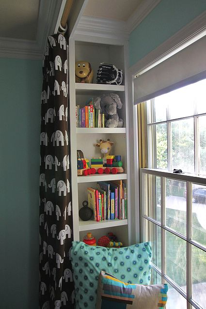 use ikea shelves and molding to make faux built-ins for toy storage. hang curtains in front. love this!  This actually makes me wonder if walls in lala'sroom adjacent to window box could be made into built ins.
