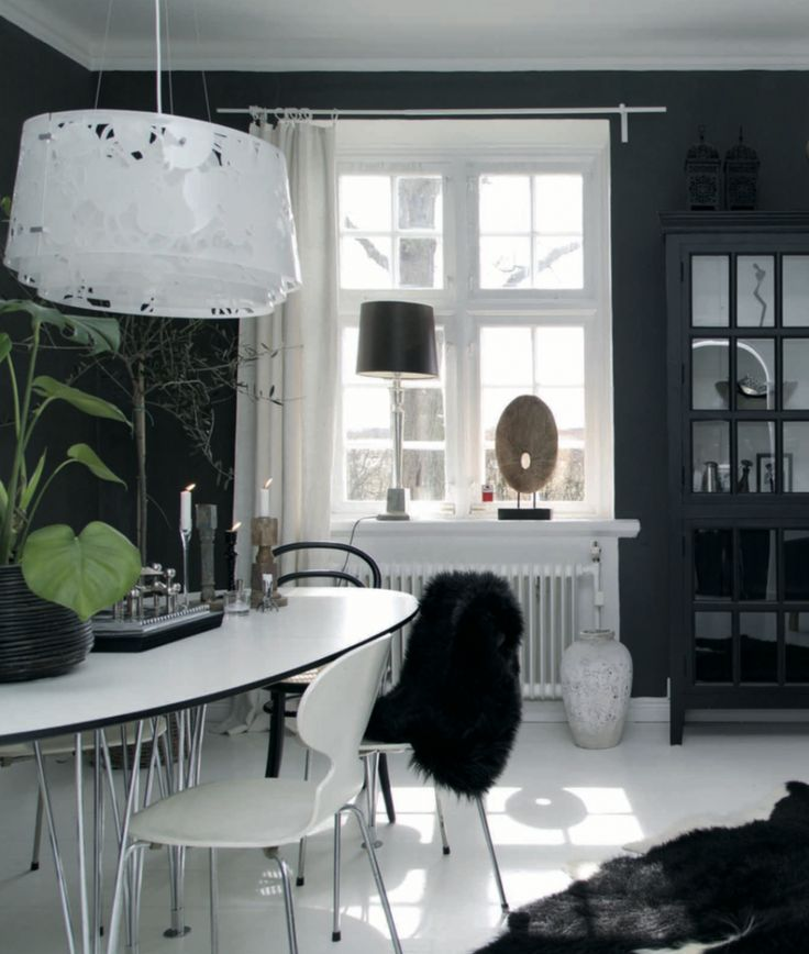 This dark grey dining room with its candles and faux sheepskins has an almost mystical feel. The leggy table is the Superellips by Swedish designer Bruno Mathsson. The lacy pendant lamp is the Collage from Danish firm Louis Poulsen, designed to provide soft, diffuse light with little glare.