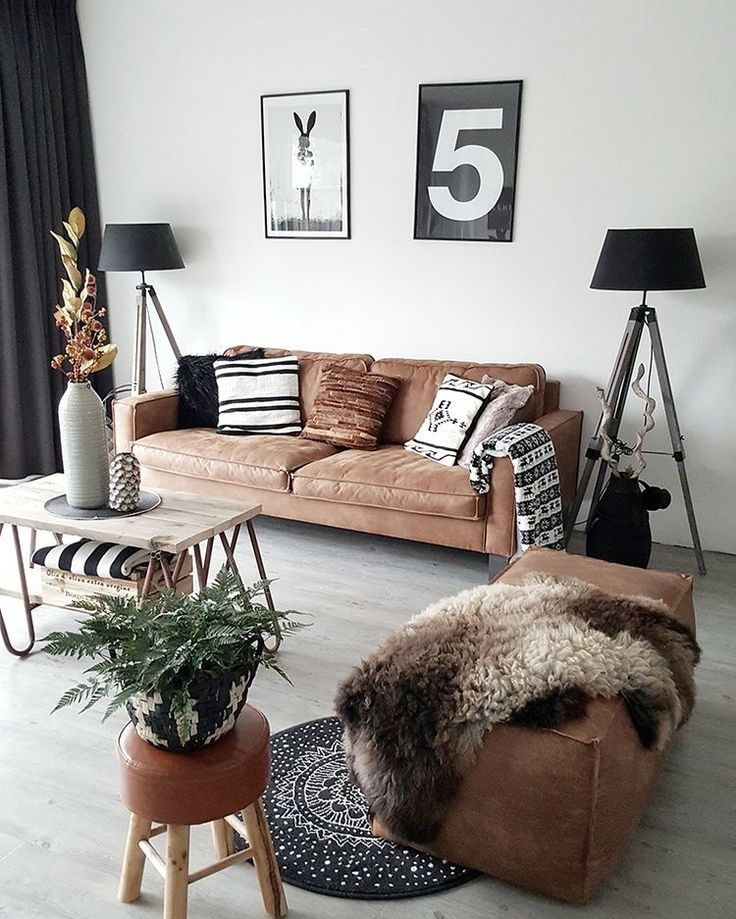 Bohemian Living Room With Light Washed Wood Floors Brown Leather Couch Black Accents