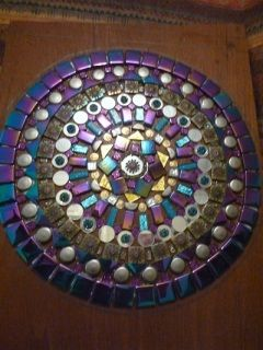 "Intricately designed and beautifully presented round mandala measuring 37cm diameter.   Mounted on upcycled timber.  Made with glass tiles, penny rounds, mirror tiles, foiled tiles, irridised tiles,  cabachons and jewellery findings (mini coins, chain and bead ends).   Glazed with diamond hard lacquer to ensure a long lasting piece.   Stacey says: ""The colours used are largely purple, pink, silver, blue, gold and aqua.""  This is a one of a kind item.   Due to it's size and fragility, this…"