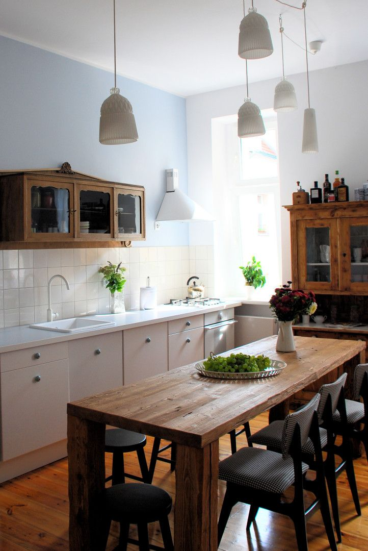 Simple white kitchen, butcher block table, antique cupboards