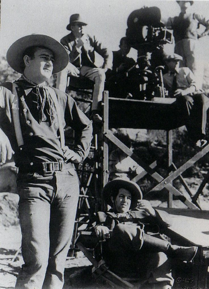 STAGECOACH (1939) - John Wayne & Andy Devine (seated in foreground) wait for the next scene. Director John Ford is seated adjacent to the camera - Produced by Walter Wanger - Directed by John Ford - United Artists - Production Still.