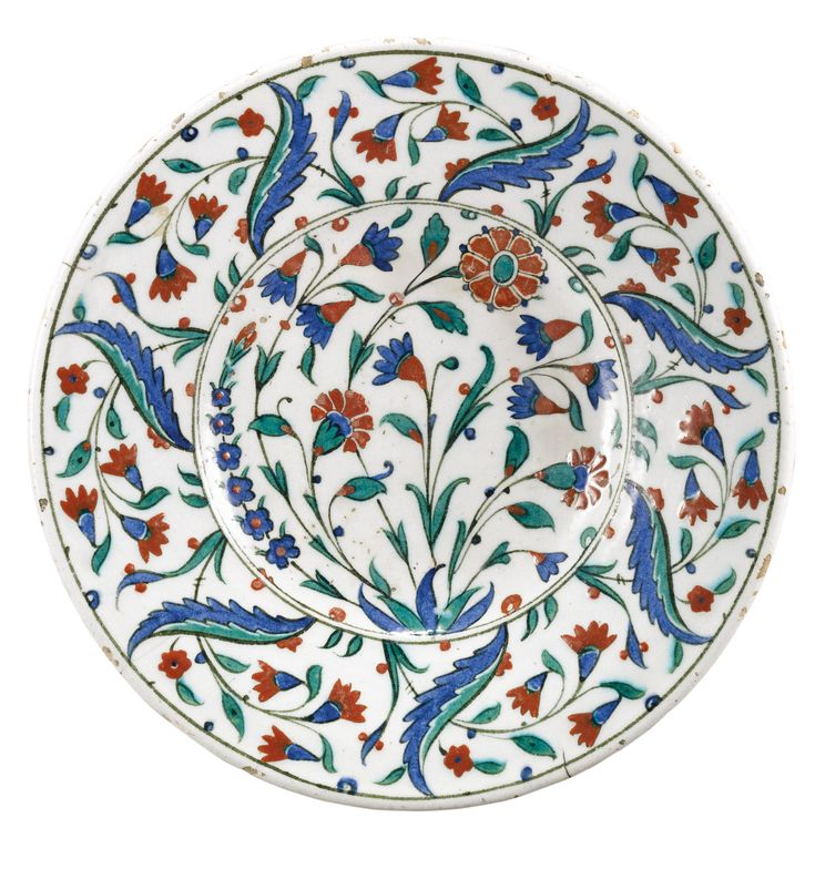 A polychrome Iznik pottery dish, Turkey, second half 16th century, of shallow round form, decorated in underglaze cobalt blue, green and relief red with black outlines, floral sprays including carnations and hyacinths, the rim with a pattern of overlapping saz leaves and floral stems.