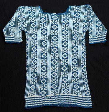 ronneby. Barntröja stickad i Bingestickning med 4-trådigt bomullsgarn i blått och vitt. Nederkant och ärmlinningar är resårstickade. Knäppning vid vänster axel med tre pärlemorknappar