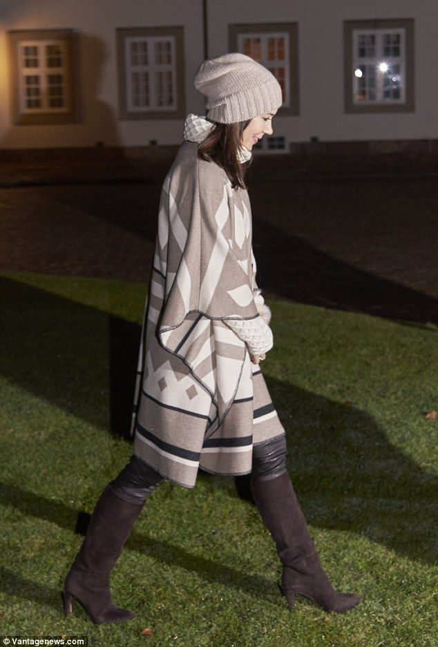 May's stylish ensemble featured knee-high suede boots, a soft knit poncho, white turtle-neck and beanie