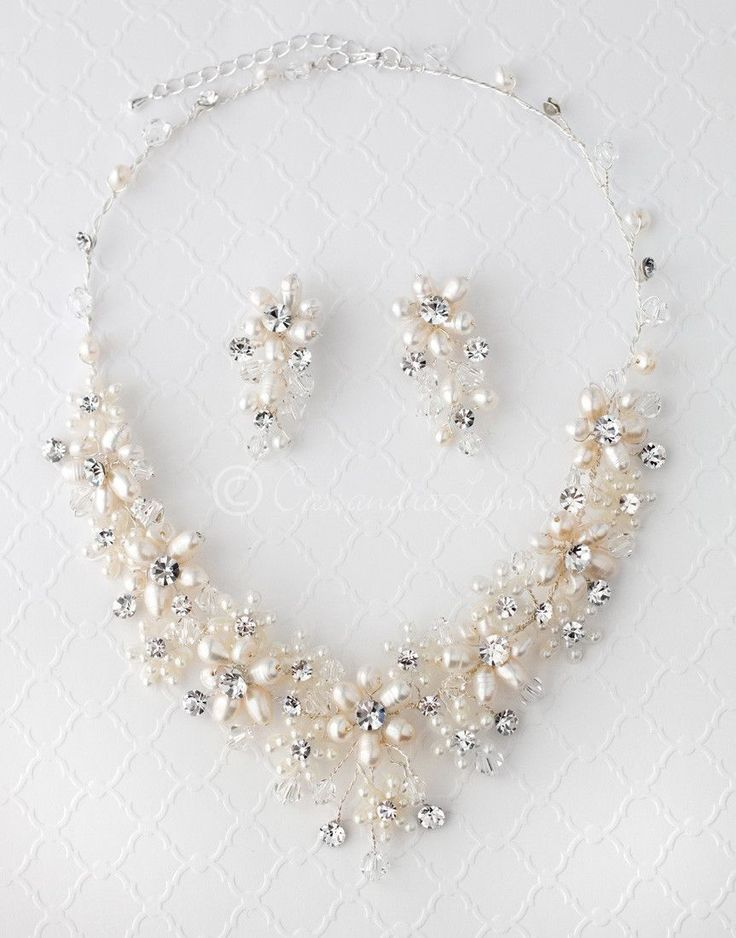 Larger ivory, cultured pearl flowers with rhinestone centers are set among smaller pearl flowers, rhinestone jewels and crystal beads in this hand wired bridal necklace set. The necklace is 16 inches long with a 2 inch extender. The earrings are 1.5 inches long with pierced post backs.
