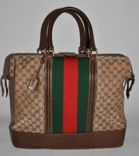 Authentic vintage Gucci vertical travel bag in brown with a key and key case that works on the lock on the body made in 60s.   GG woven canvas is with light wrinkles but there is no fray or marks, is clean. Brown leather handles are firm without marks or wear. Brown leather strips on the body is with small amount of light abrasion without worn through. Brown leather on the bottom is with small amount of light abrasion and light scratches. Zipper has darkening but it works perfectly. Lining…
