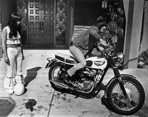 Cher next to Sonny kickstarting his Triumph