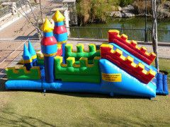 """Knights Den - This interactive inflatable is very popular, it consists of a jumping surface with obstacles , another enclosed section just for jumping and a combat net that kids can climb up or down onto a slide. Great to use as part of a """"Medi Evil"""" themed party. Suitable for boys and girls."""