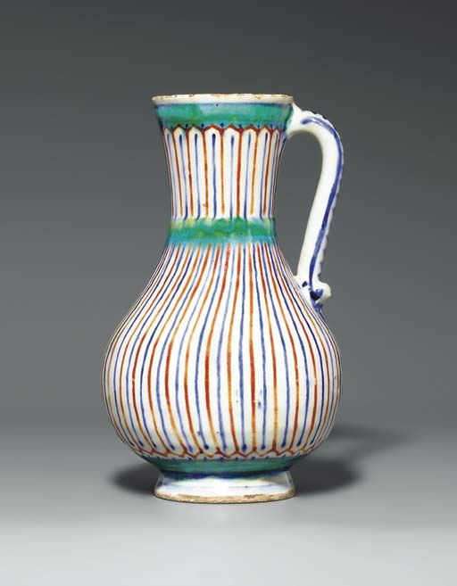 AN IZNIK POTTERY JUG OTTOMAN TURKEY, CIRCA 1565 Of baluster form on short foot rising to flaring trumpet mouth and with simple loop handle, the white body decorated with stripes of cobalt-blue and bole-red, bands of blue and greenish-turquoise above the foot, at the waist and below the mouth, mouth slightly chipped, hairline crack to mouth, handle with slight restoration 9¼in. (23.6cm.) high