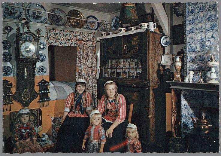 Twee Marker vrouwen met drie kinderen, allen in dracht, poseren in een Marker interieur. O.a. Friese bruidsstaartklok (met latoenkoperen rand om de wijzerplaat, ruitertjes en gesneden kast) en betegelde schoorsteenmantel. 1950-1970 #NoordHolland #Marken