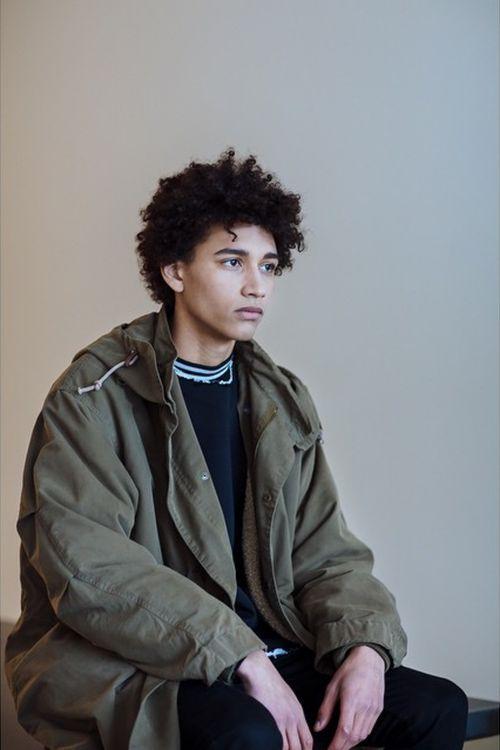 Zwart haar - donkere huidskleur - groene jas