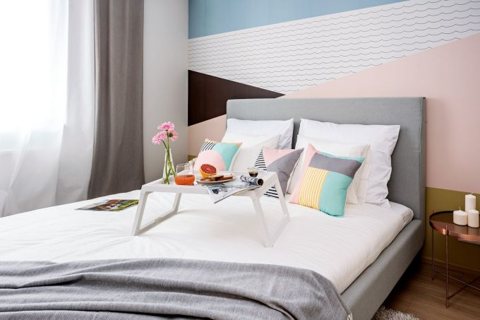 Ložnici dominuje čalouněná postel Kent značky Vivonia od Bonami, vestavěné skříně jsou vyráběné na míru u firmy Indeco, tapeta Lavmi