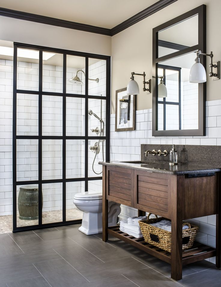 """""""This bathroom was a fun room to design,"""" says Kathryn. """"It acts as a changing room for the pool and bathroom for the living area. Since it has no natural light, we created the look of a skylight by installing a dropped ceiling and adding a recessed glass case with frosted glass and daylight bulbs."""" The paned shower wall brings in another industrial accent."""