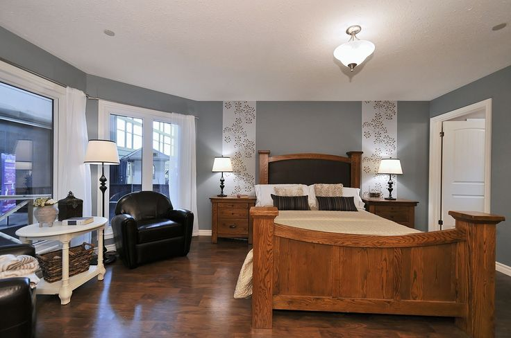 The Trent Master Bedroom by Quality Homes....slate blue walls, wood floors, large oak bedroom furniture, seating area, ensuite & walk-in-closet attached...  www.qualityhomes.ca