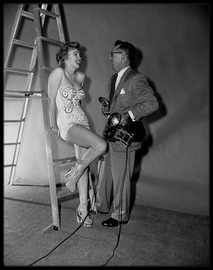 """1952 / Dans les coulisses du tournage et d'une session photos avec Earl THEISEN pour le film """"We're not married"""" / SYNOPSIS / Un ensemble de cinq histoires entremêlées sur cinq couples qui, deux ans et demi après avoir été unis par les liens du mariage, découvrent qu'ils ne sont pas (et n'ont jamais été) mariés.  En effet, le juge de paix qui les a unit, Melvin BUSH (joué par Victor MOORE), a célébré les cérémonies quelques jours avant que sa licence ne soit valide. Marilyn interprète la…"""