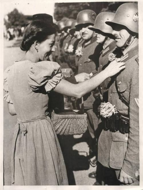 A local girl pinning a flower on a German soldiers uniform in Olbersdorf as Nazi forces occupy the Sudetenland. 1938