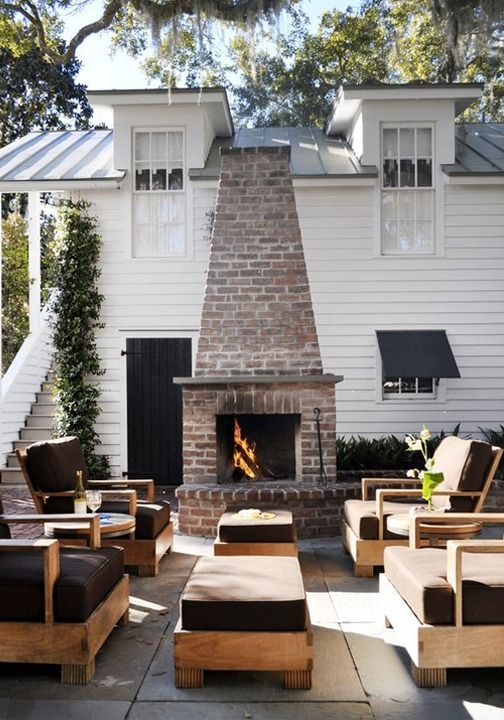 Create the perfect outdoor entertaining area with comfy patio furniture and a cozy brick fireplace.