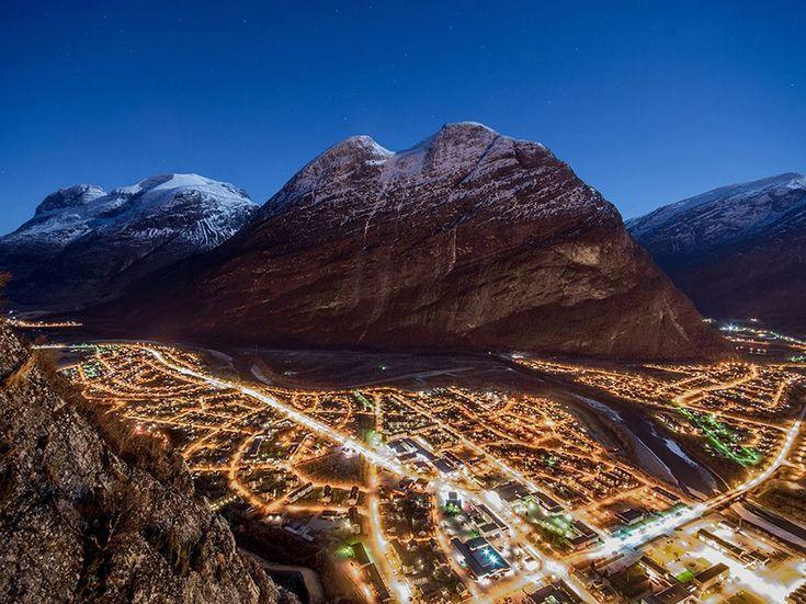 Luci del Nord Fotografia di Christian Nesset , National Geographic Your Shot  Veduta notturna di Sunndalsøra, Norvegia, una città circondata da montagne spettacolari