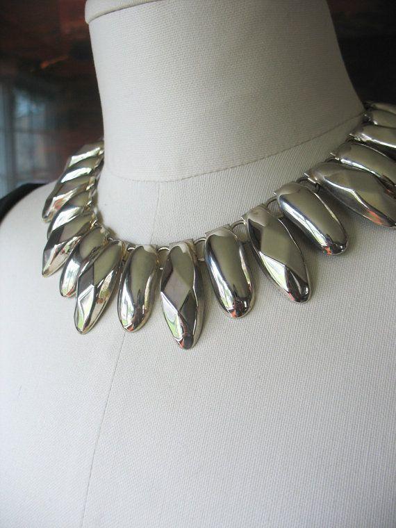 Vintage des années 1970 Tribal dopés collier dans une plaque d'argent vif et brillante. Ce magnifique collier en vedette des pièces de métal à facettes qui offrent un look tribal sophistiqué. Le collier a un bon poids à elle, mais pour ne pas lourd, car il est très agréable à porter.  Longueur : 16 » Plus grande perle: 1 1/2 « x 1/2 » Matière : Métal plaqué argent Construction : Connecté avec les liens de lanneau et se ferme avec un fermoir crochet. Datation : 1970-1980 Trapu, style...
