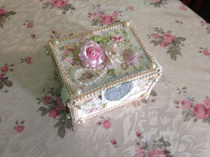 Frente de la caja. Un corazón hecho con brillantinas y diamantitos de fantasía, y arriba de la misma, perlas, flores de tela, mariposa hecho con alambre y tela de tul.