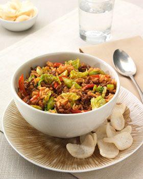 Kook de rijst volgens de aanwijzing op de verpakking. Afgieten in een vergiet en laten uitlekken. Snijd ondertussen de Chinese kool en de paprika in reepjes en de lente-uitjes in ringetjes. Pel de teentjes knoflook en hak ze fijn. Verhit een wok, voeg de Conimex Wok Olie toe en roerbak hierin het gehakt 3 min. Giet overtollig vocht uit de wok. Voeg de paprika, de Chinese kool en de knoflook aan het gehakt toe en wok 5-6 min. mee. Voeg dan de rijst toe en roerbak nog 2 min. Voeg de Conimex…