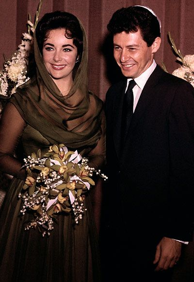 "Husband #4: Eddie Fisher  Year: 1959  Profession: Singer  Details: The destination was Vegas for Taylor and Fisher's wedding at a local synagogue. Taylor took a fashion gamble choosing a green silk hooded dress for this occasion. ""It was a typical two-rabbi Jewish ceremony,"" Fisher wrote in his autobiography Been There, Done That. ""As usual, Elizabeth was late for her own wedding.""    In a much talked-about romance, Taylor married Fisher less than a year after Todd was killed."