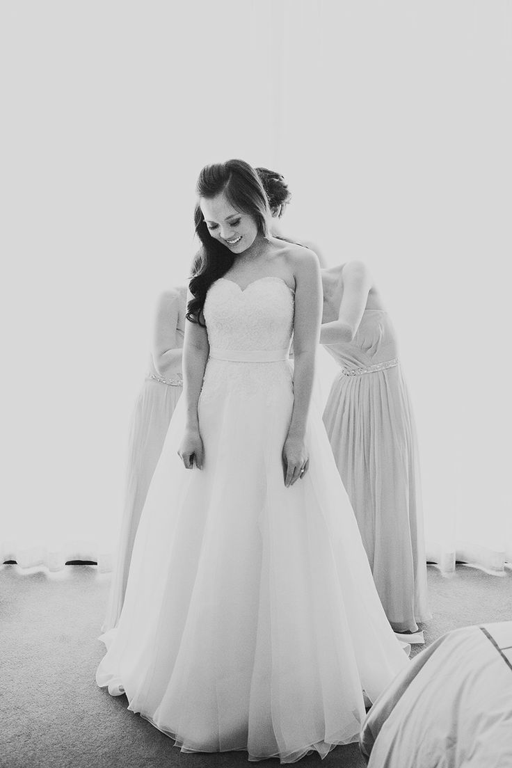 Bridesmaids helping bride get ready. Beautiful shot. (Wedding, style, bridal gown, dress, photography)