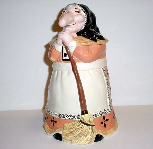 "Baba Yaga, the Scandinavian Autumn Crone, is the inspiration for this very traditionally styled ""kitchen witch""; cookie jar. According to legend, the presence of the kitchen witch will ""protect your kitchen from fires, keep your bread from falling and scare away evil spirits."" Not bad for a cookie jar!    This Kitchen Witch is painted in earth tones with a black head scarf holding her handy broom."