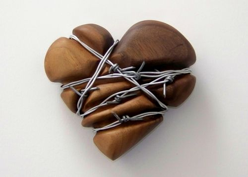 Keep Out, I really mean it. By Robert J Knight.  Carved walnut heart, with several strands of barbed wire wrapped as though they have been there a long time, and have deformed the heart.  (Who has not felt like this at least once?)