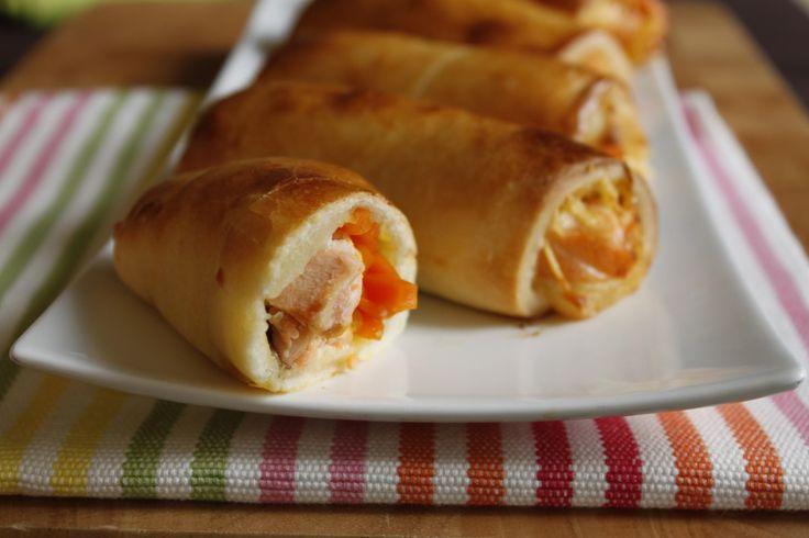 Préchauffez votre four Th.7 (210°C). Epluchez et hachez l'ail et l'oignon. Epluchez et coupez les carottes en bâtonnets. Faites-les revenir avec l'ail et l'oignon dans une poêle avec l'huile d'olivependant 2 minutes. Ajoutez le jus d'orange et laissez réduire. Emiettez le bouillon et mélangez. Laissez refroidir. Découpez la pâte à pizza en 8 morceaux égaux. Coupez le saumon en 8 bandes égales. Placez un morceau de saumon, des bâtonnets de carottes au bord de chaque morceaux de pâte…