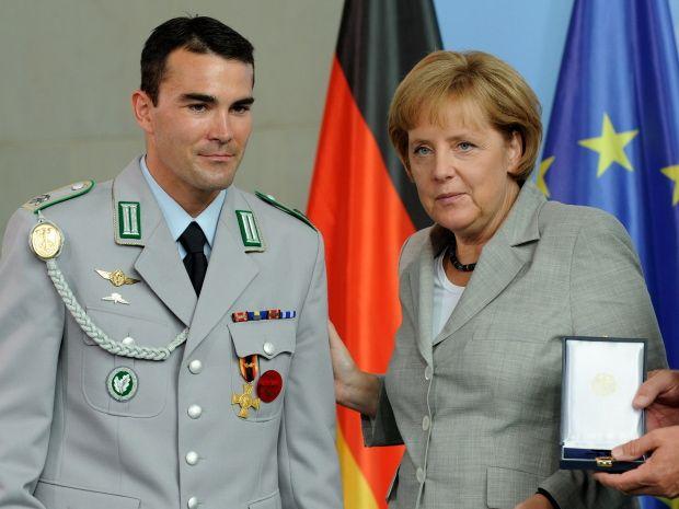 Bundeskanzlerin Angela Merkel (CDU) verleiht dem Oberfeldwebel Markus Geist das Ehrenkreuz der Bundeswehr für Tapferkeit. -Foto: dpa