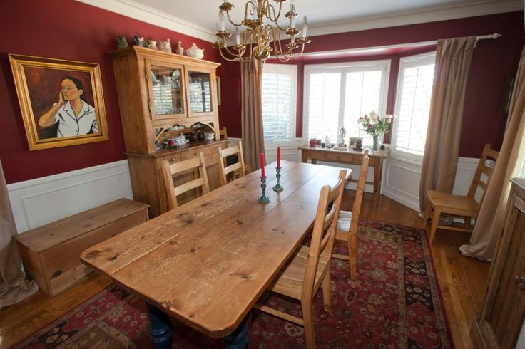 "In the dining room, rustic wood furniture enhances the home's French country style, while a large bay window frames views of the front yard. ""[The neighborhood] feels like the East Coast because we have tall trees and large yards,"" Beth says. ""The neighbors are very friendly and kind."""
