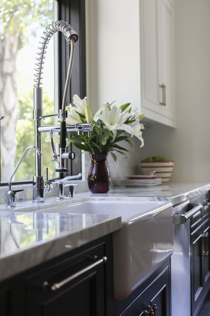 French Contemporary Traditional Kitchen: A farmhouse sink with commercial faucet in a light-filled L.A. kitchen.
