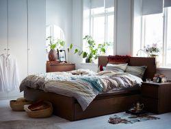 Chambre à coucher de taille moyenne meublée avec un lit double brun complété par des tables de chevet et une commode.
