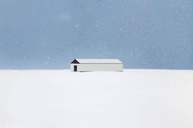 Hangar près du village de Dalvík, sur la côte nord de l'Islande, Bienvenue sur l'île des tempêtes de neige. Le photographe Christophe Jacrot est tombé sous le charme des paysages islandais et s'est enfoncé dans le blizzard afin de capter la beauté fantomatique de l'hiver.La neige embellit tout, même ce simple hangar agricole au milieu d'un champ, près du village de Dalvík, sur la côte nord. Avec ses lignes géométriques épurées, en noir et blanc, il ressemble à une installation de land…