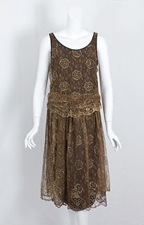 Metallic lace flapper dress, c.1925. Made from bronzed metallic lace over a black satin lining, this scintillating dress slips on without closures. The lower sides of the bodice are ruched, creating a cummerbund effect. The scalloped border on the lace is of the last degree of charm. The incandescent beauty of the lace personifies the dazzling splendor of 1920s fashion.