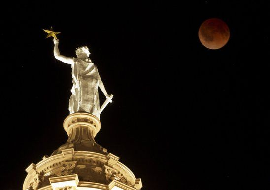 The moon turns red during a total lunar eclipse over the Goddess of Liberty statue atop the Capitol in Austin, Texas.