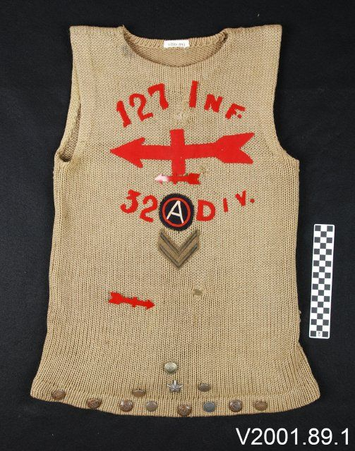 Vest, wool, olive drab, hand knit w/one sideseam. Embellishments added by veteran to the front of the vest starting at the neck opening, wool felt, red, 127 INF./a red arrow, wool felt/a plastic red arrow pin/32, a theater produced Third Army patch, wool, red, white and blue, DIV./two overseas chevrons made of bullion wire/and another plastic red arrow pin.