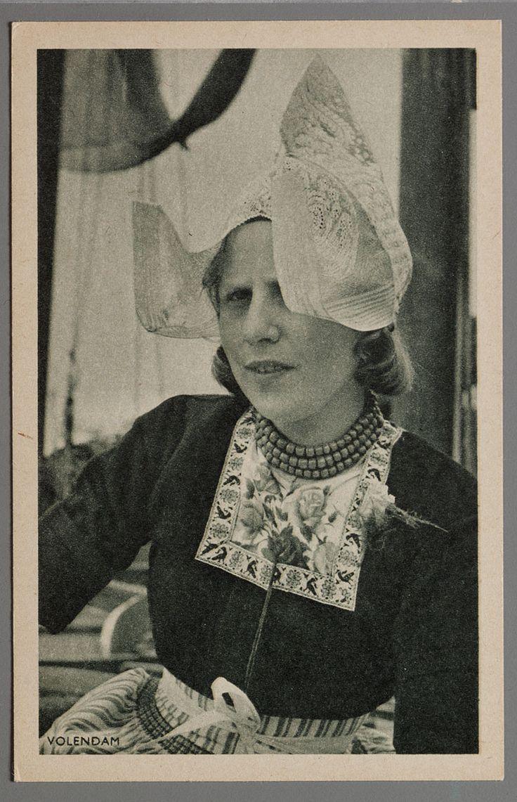 Portret van Gaar Koning (Koopman), Volendamse vrouw, half totaal, met kanten muts (hul), kletje, bloedkoralen ketting en gestreept schort. Op haar linker schouder draagt ze een corsage (anjer). 1950-1960 #NoordHolland #Volendam