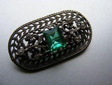 Z obecného kovu, s imitacemi smaragdu a briliantů ze skla. Sklo v barvě smaragdu má dokonalou barvu i výbrus. Brož je vynikající práce.   Rozměr 4,2 x 2,5 cm. Velmi pěkný stav. Okolo roku 1920  Jablonecko  Šperky s imitacemi drahých kamenů jsou jedinečným důkazem mistrovské práce Jablonecka.