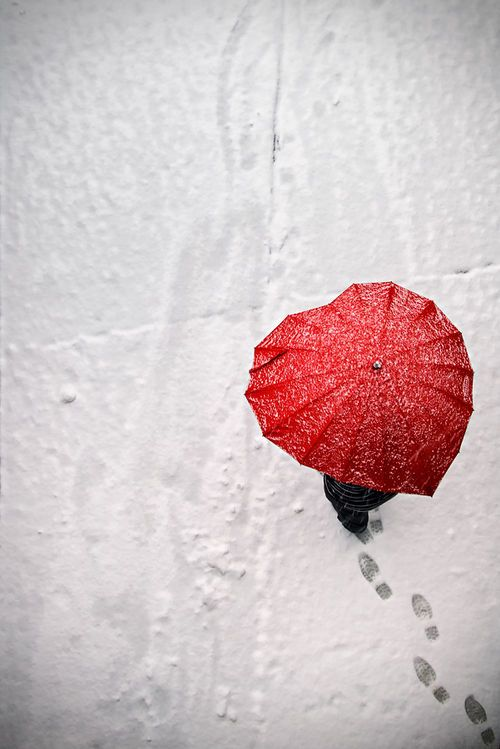 Footsteps on the snow. This is just a beautiful picture. The contrast of the white snow and red umbrella.