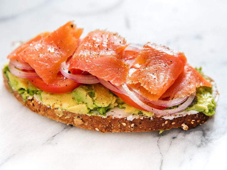 This bagel-and-lox-inspired open-faced sandwich combines avocado and smoked salmon, cut through with tomatoes, capers, and thinly sliced rounds of red onion. Goat cheese takes the place of cream cheese for extra tang, while a squeeze of lemon juice and a little fresh black pepper bring everything into balance.