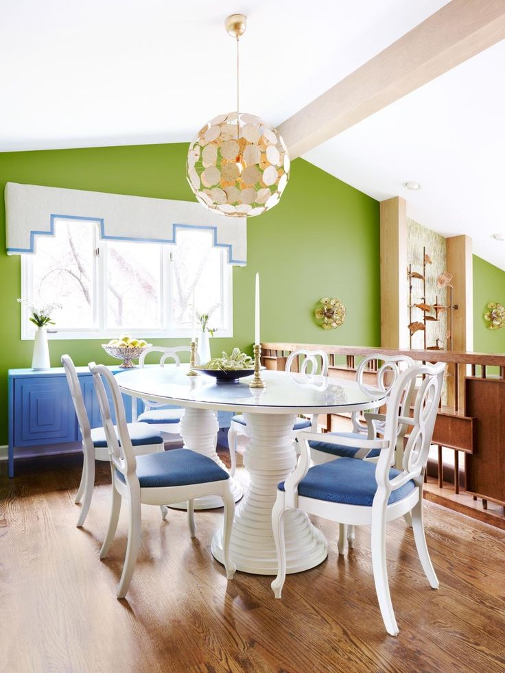 A modern dining room with round table and chairs and a large, round pendant light hanging above.