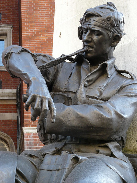 Croydon War Memorial (detail), a wounded soldier struggles with his own dressing. Memorial situated on  Katherine Street, Croydon, London