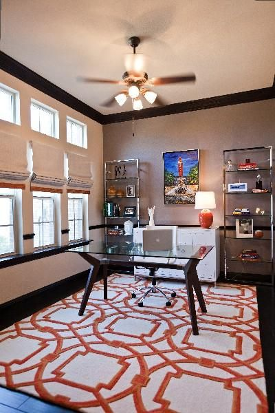 dens/libraries/offices - Arabesque Rug-Coral taupe gray walls modern chic polished nickel bookshelves towers glass-top desk linen roman shades orange ribbon trim: Ideas, Area Rugs, Living Room, Desks, Ten 25, Orange Rugs, Studios Ten, Home Offices, Abb Fenimor