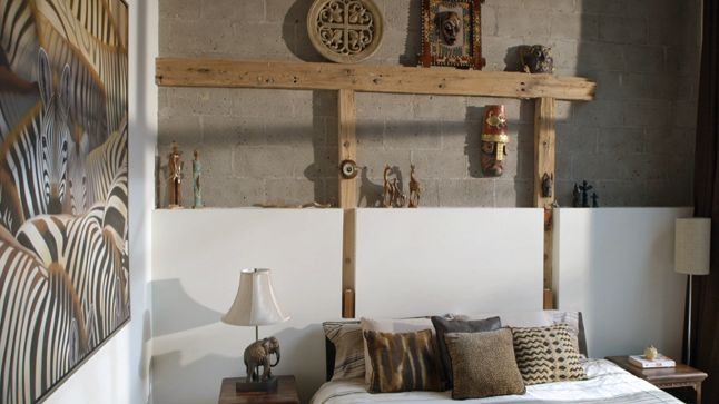 Dans cette chambre, le bas de mur de gypse et les poutres de bois verticales sont des éléments architecturaux très intéressants visuellement, permettant également une exposition de souvenirs de voyage structurée et esthétique en plus de servir de tête de lit des plus uniques.